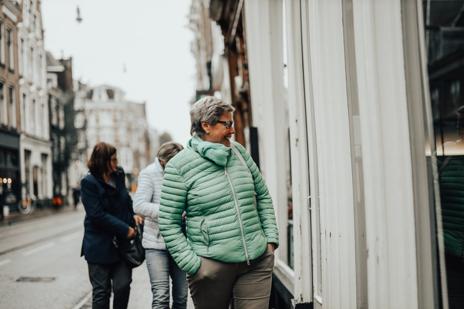 a woman in a green winter jacket walking on the street and looking in a window while smiling