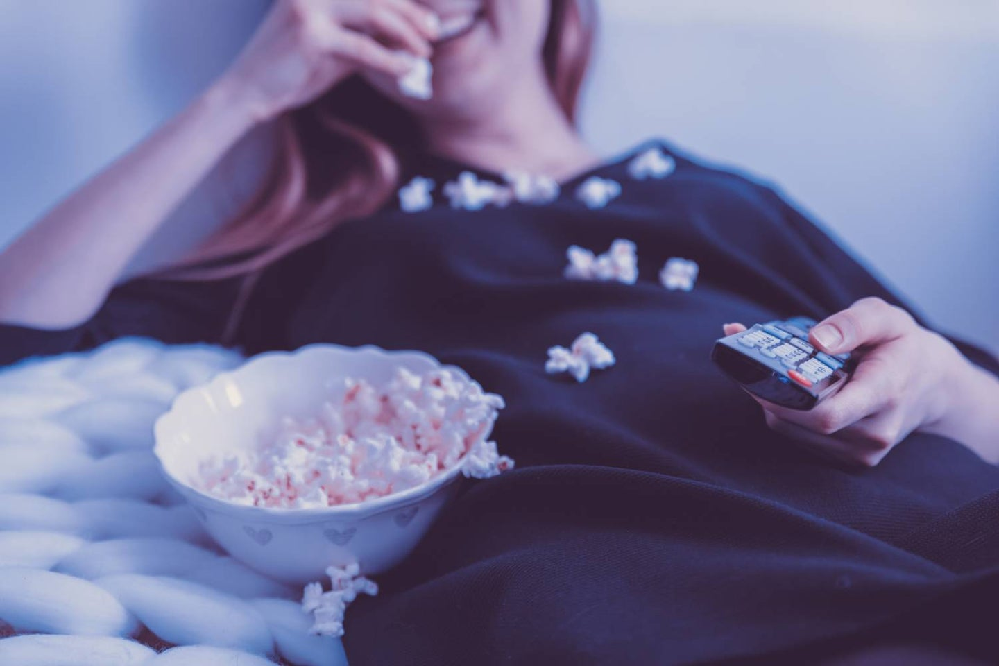 Person watching TV and eating pop corn