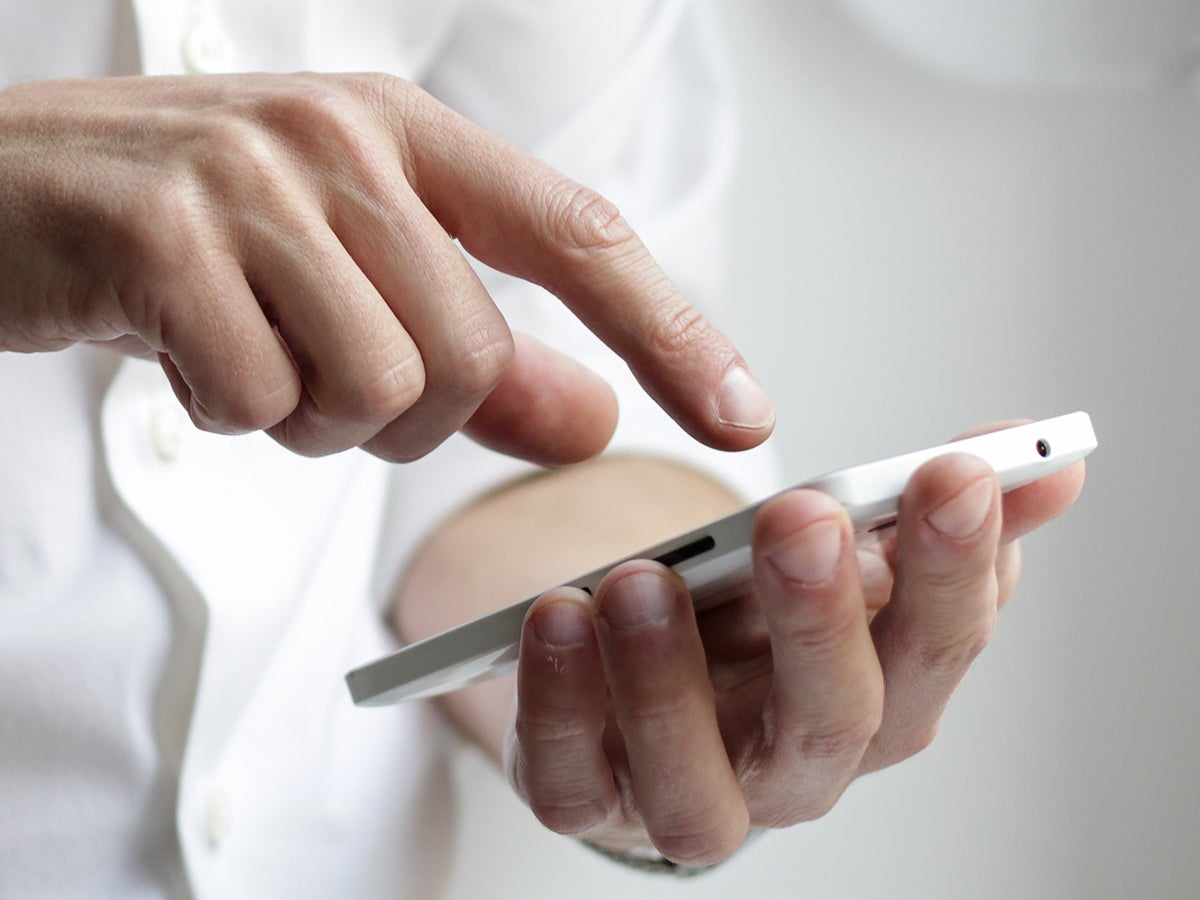 a person in a white shirt holding a phone and using it