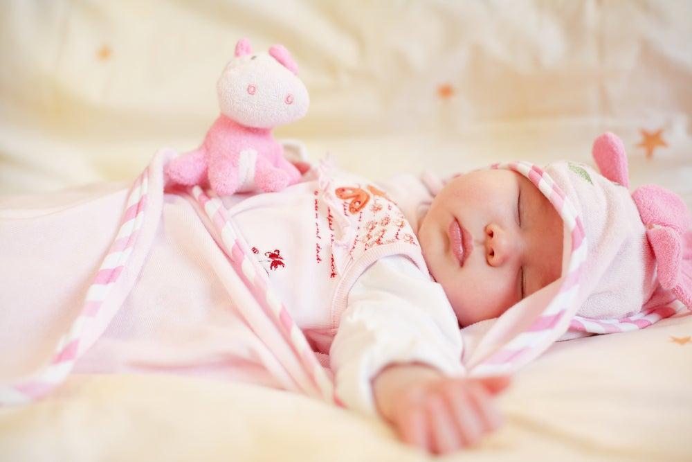 Sleeping baby with small teddy bear