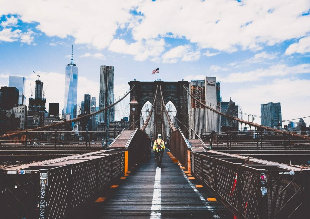 a man walking alone on the brooklyn bridge with the NYC skyline and an American flag visible