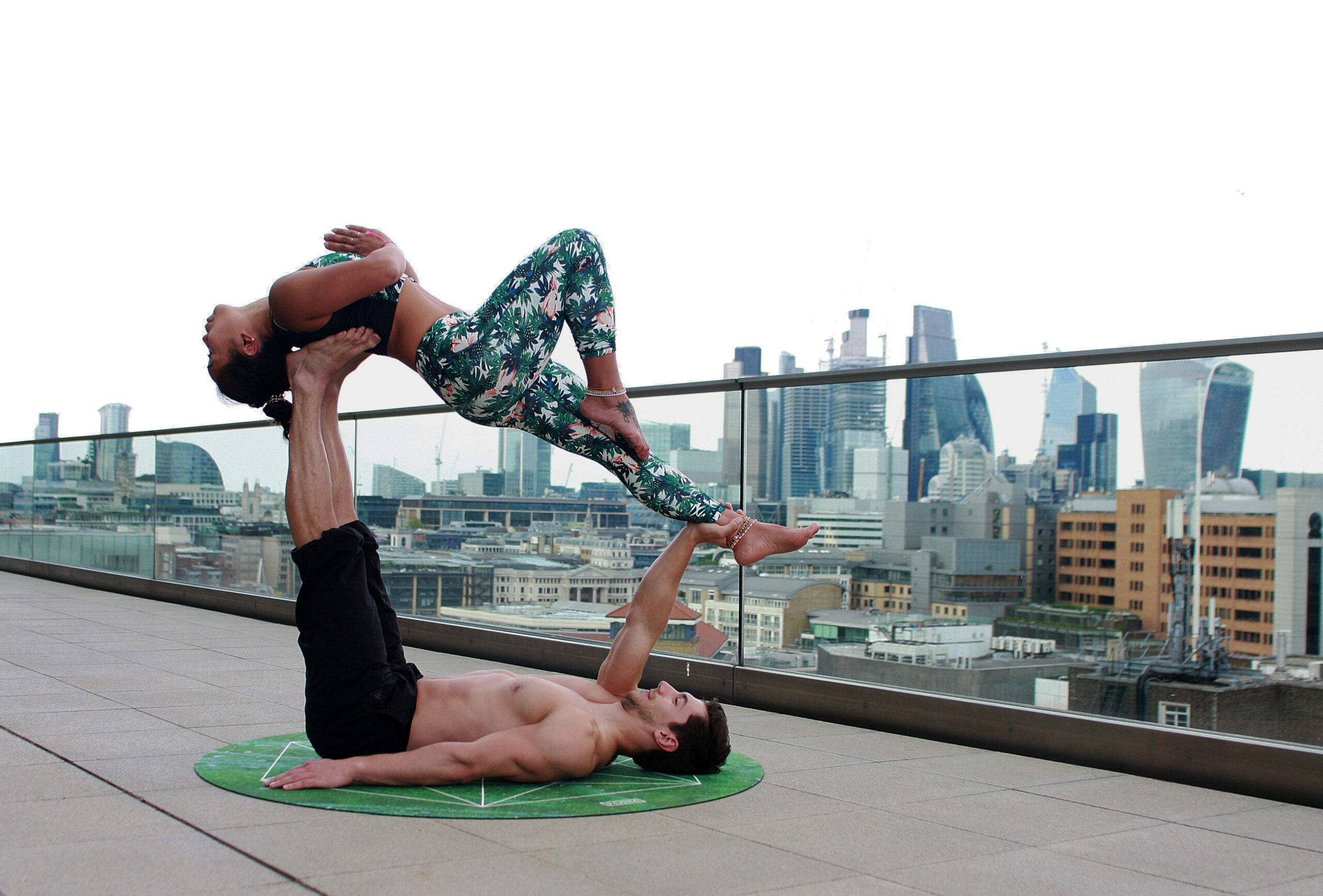 Two yoga practitioners posing on a roof