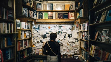 a person standing in front of a wall with a lot of notes on it, surrounded by books