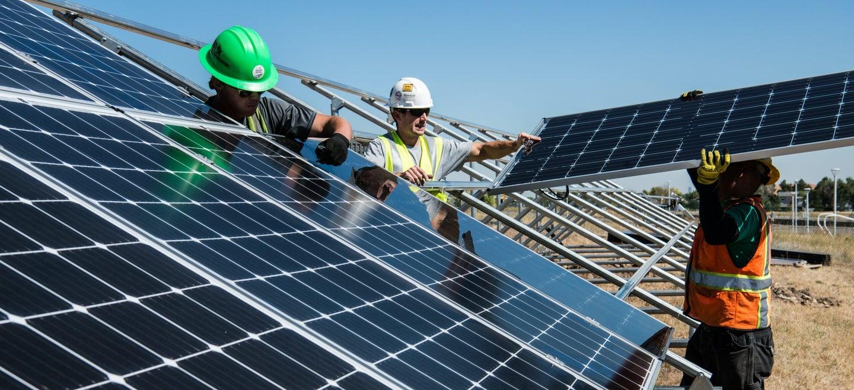people assembling solar panels