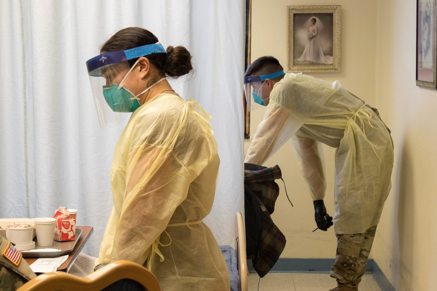two people in protective gear stand by hospital beds