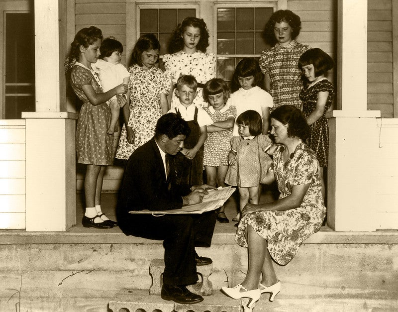 A black and white photo of a census taker with a big family full of children