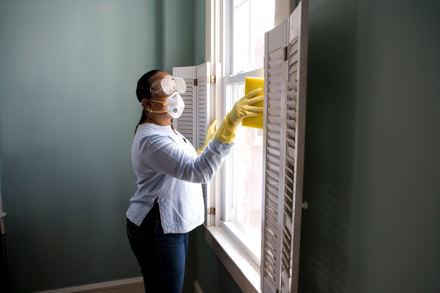 a woman wearing a face mask, goggles, and gloves while cleaning a window with a sponge