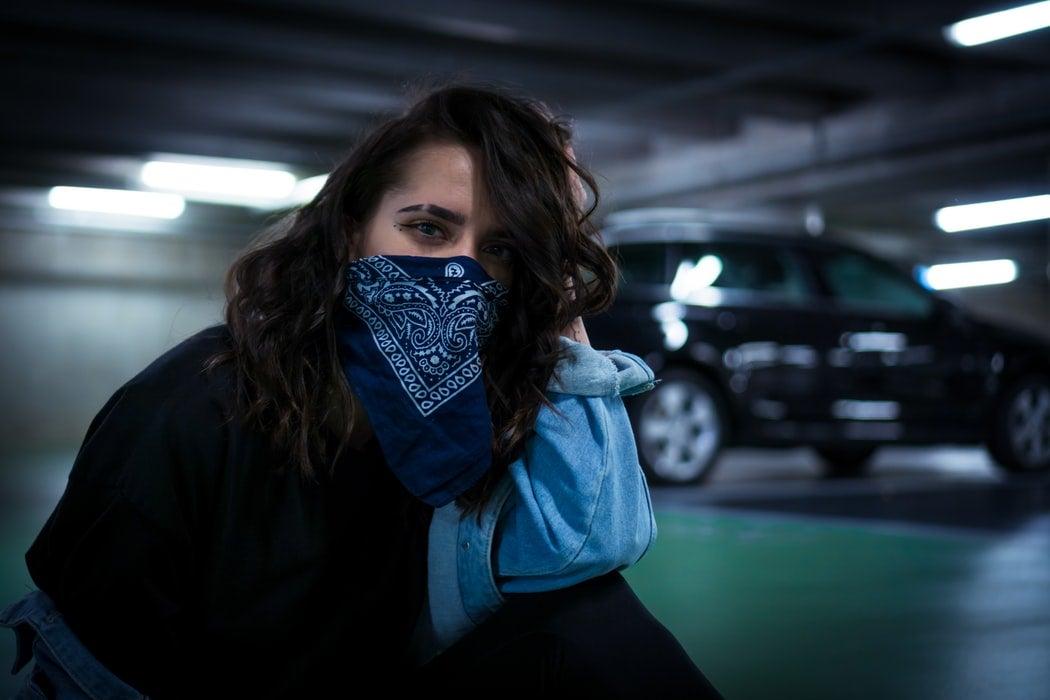 a girl wearing a bandana around her face