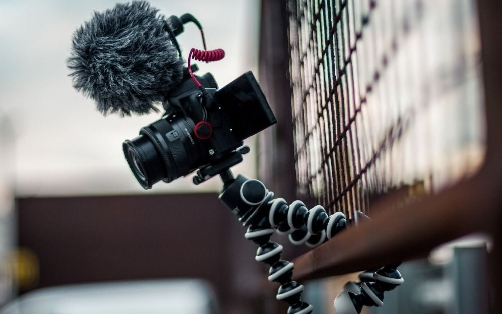 A black professional camera hanging over a wooden fence.