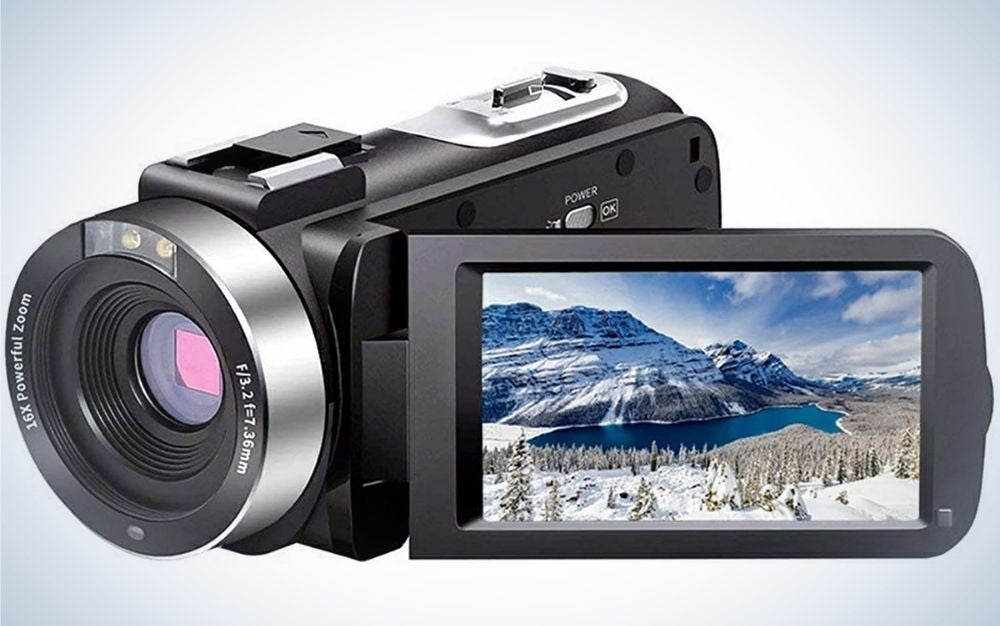 A black and silver professional camera with a small desktop with a mountain view in it.