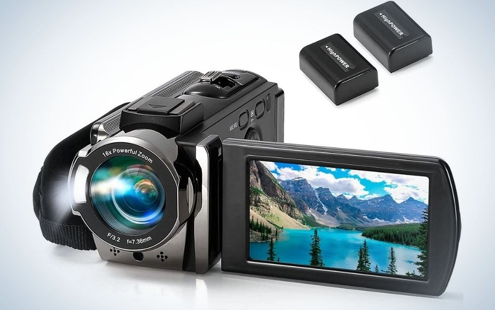 A black and silver professional camera with a small desktop with a mountain view in it and with two high power black batteries.