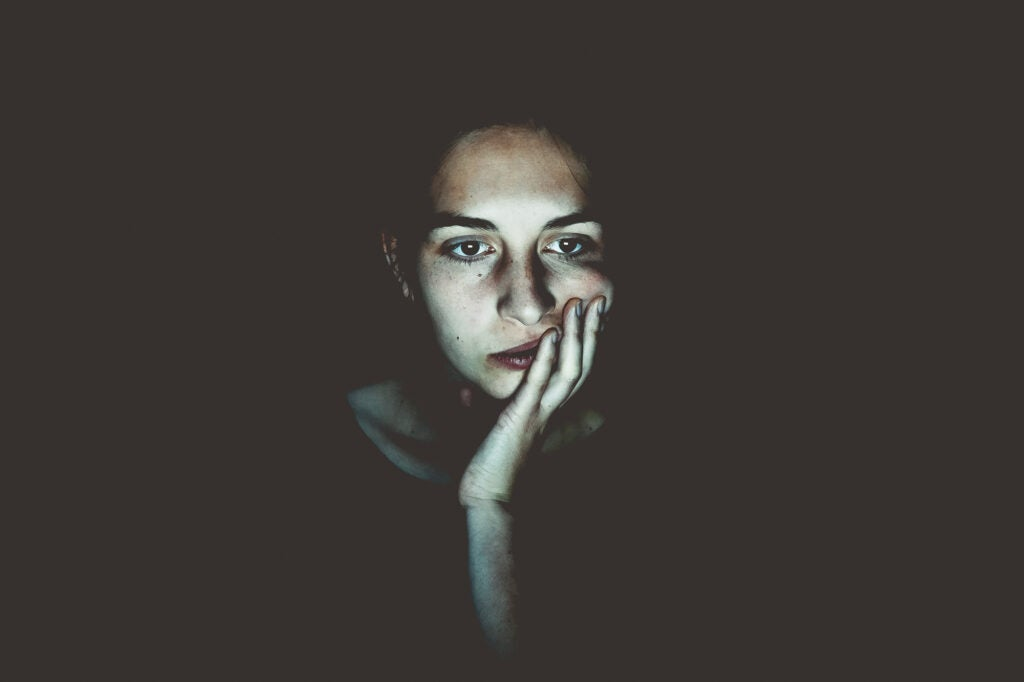 Person staring at laptop screen in the dark