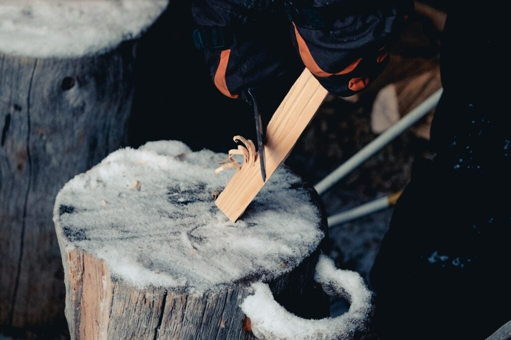 a person carving wood on a log covered in snow