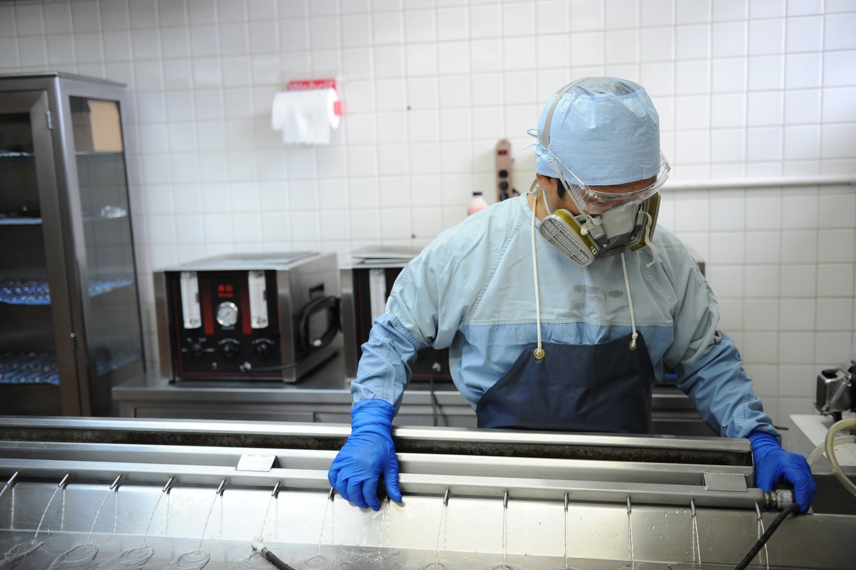 person in protective gear in a morgue