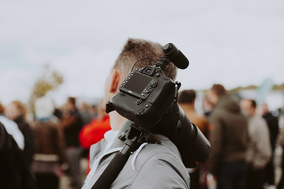 camera with attached microphone over someone's shoulder
