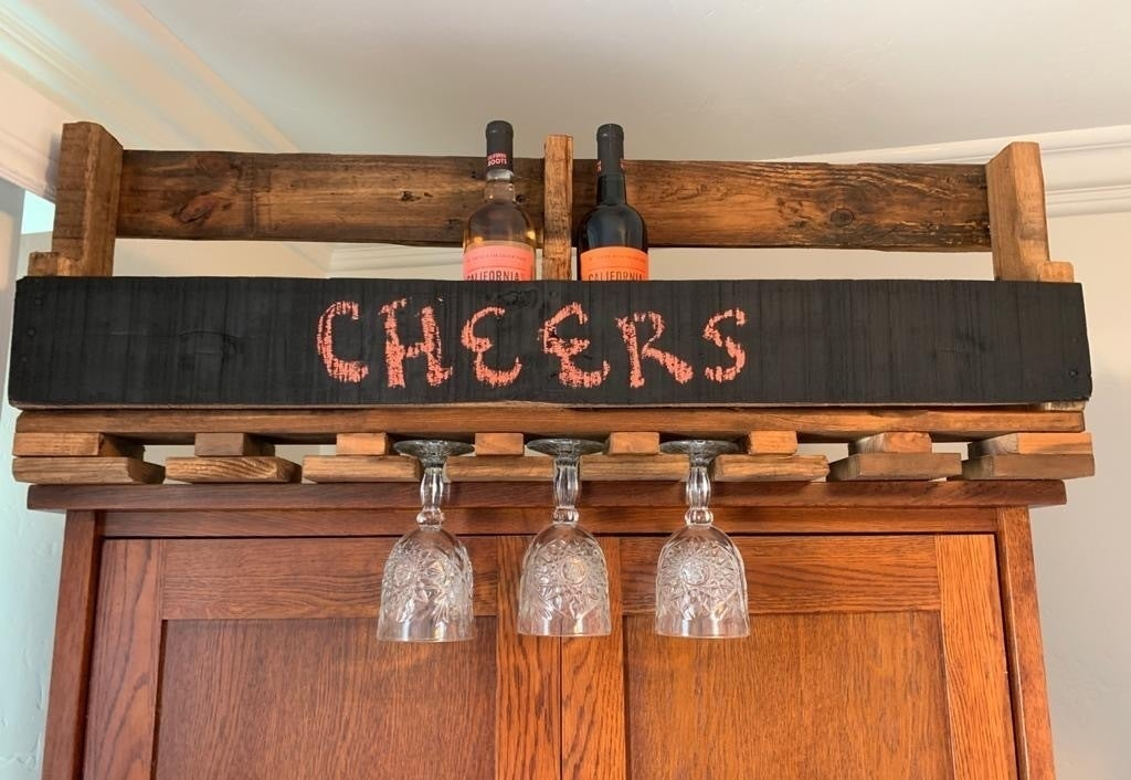 a wall-mounted wine rack made out of a reclaimed wood pallet, with a chalkboard and a wine glass holder