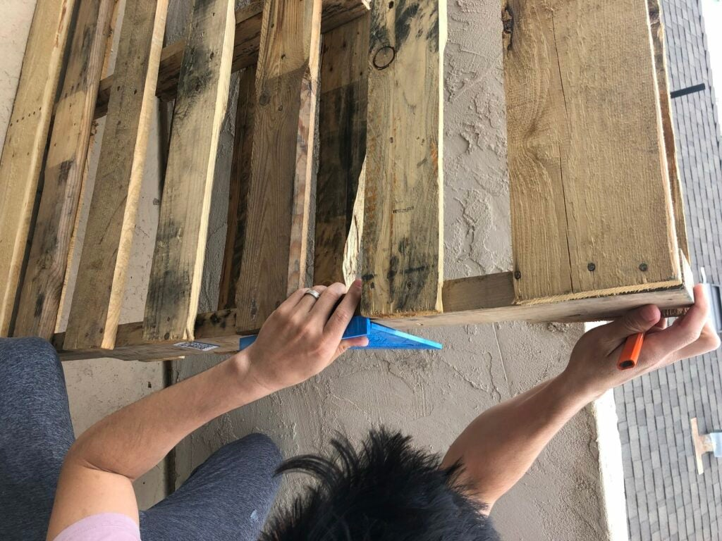 a person marking where they want to cut on a wooden pallet that will eventually become a wall-mounted wine rack