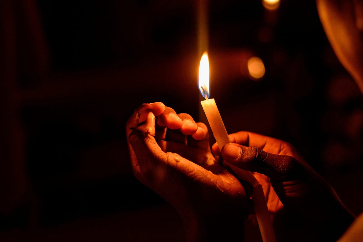 Hands holding candle.