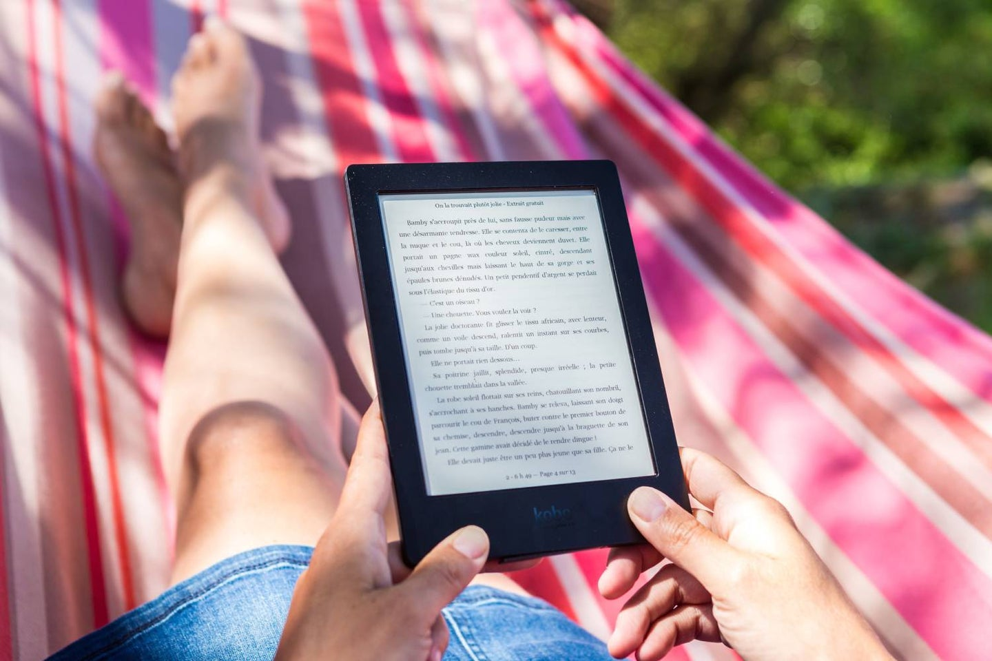 A person reading with an e-reader in a hammock outside.