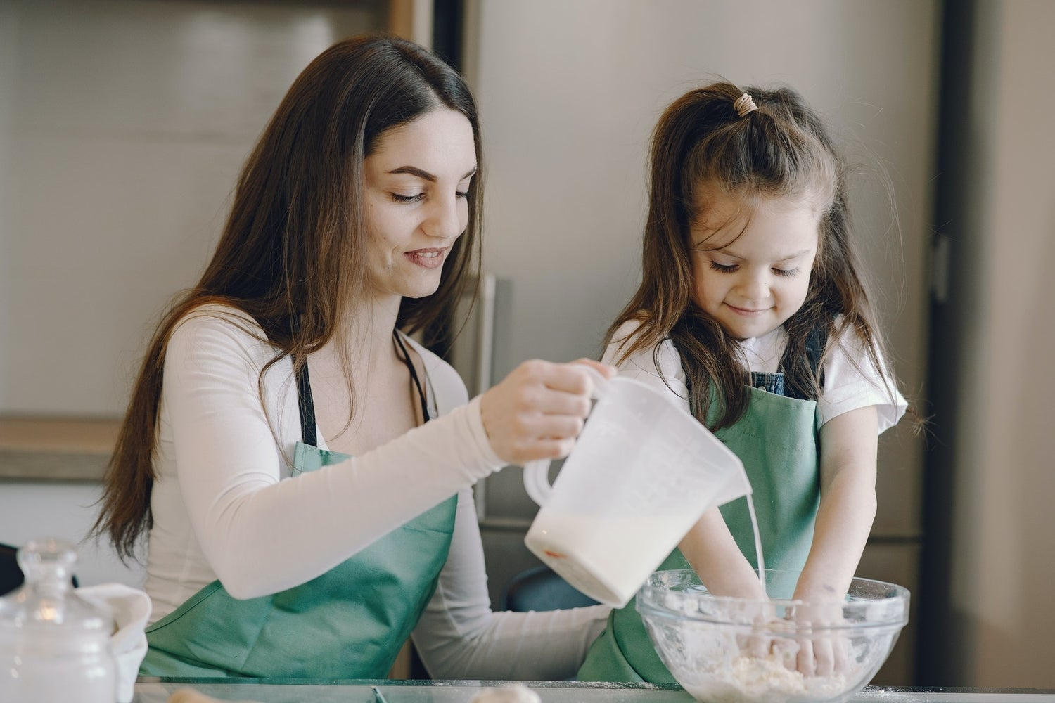 a woman and a child mixing materials in a bowl while wearing aprons, perhaps they are making a science project