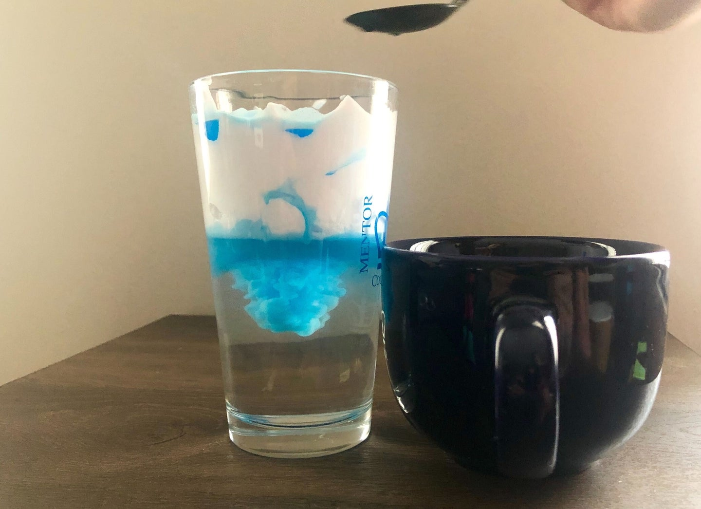 a photo of a person pouring colored water into a glass of shaving cream and water to demonstrate rainfall with a science experiment project creating a storm in a glass