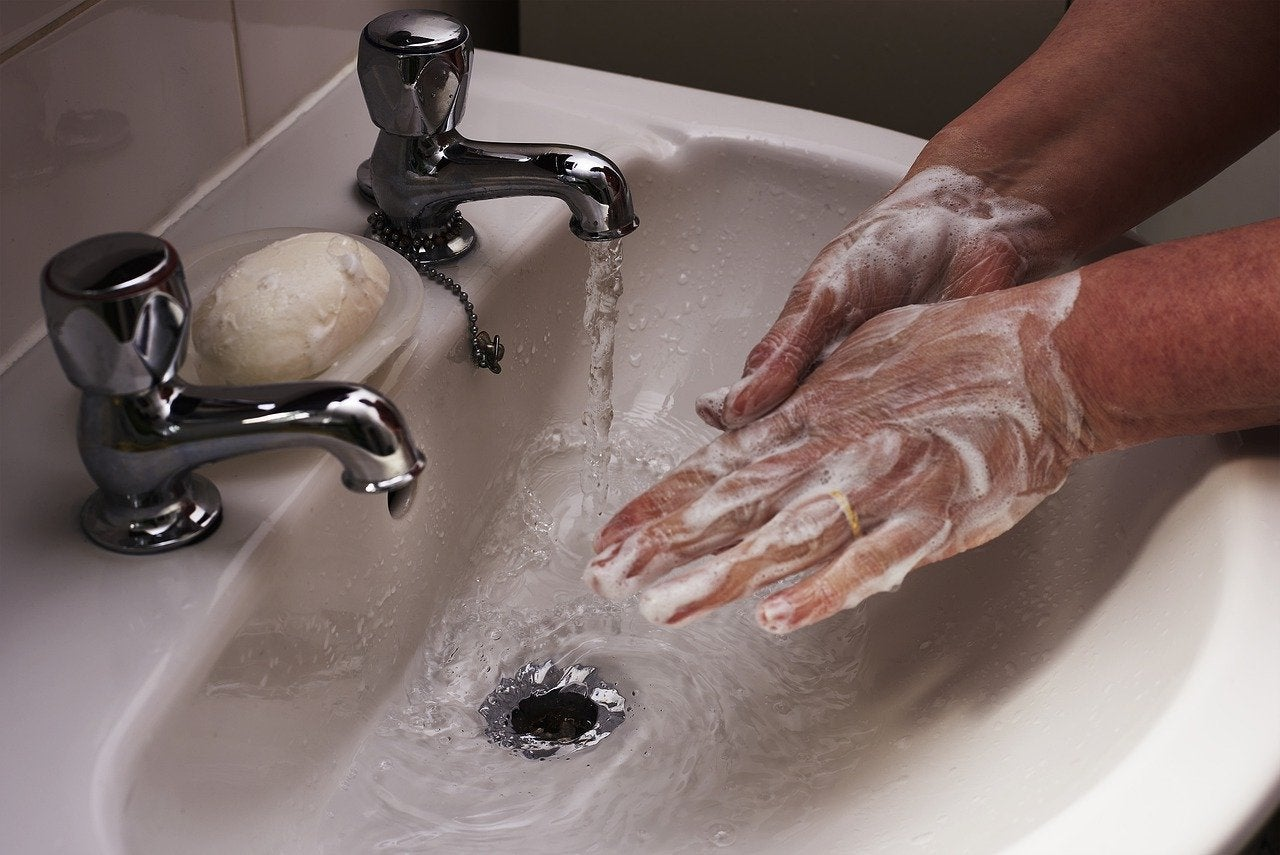 Person lathering hands under a running faucet