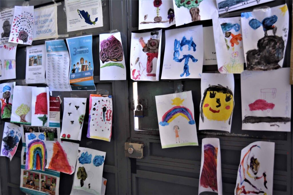 Children's art papers the walls of the Movimiento Juventud 2000 migrant shelter.