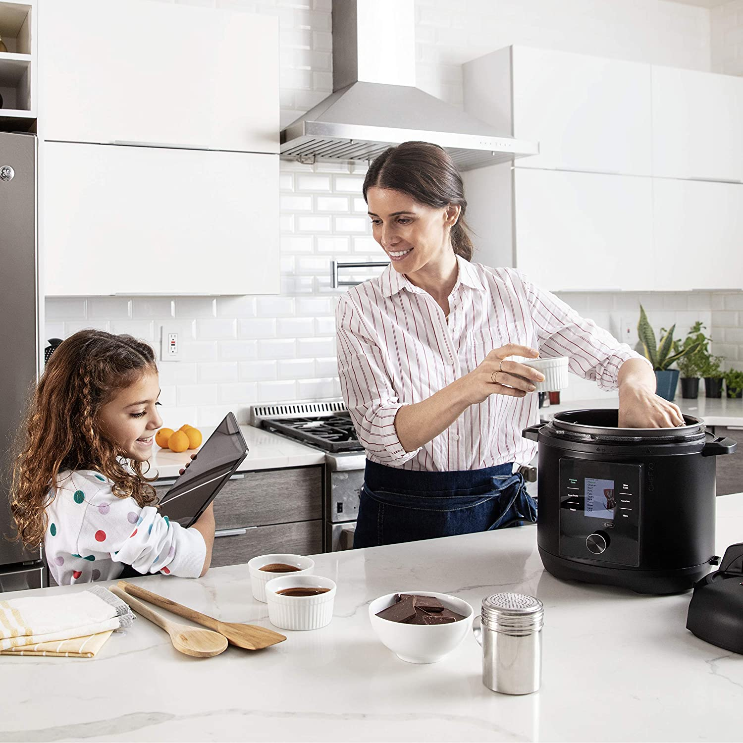 mother and daughter making food in multi-cooker