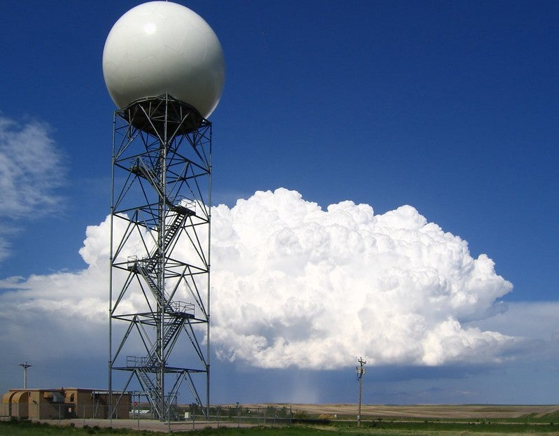 A weather radar station in South Dakota with a thunderstorm in the background