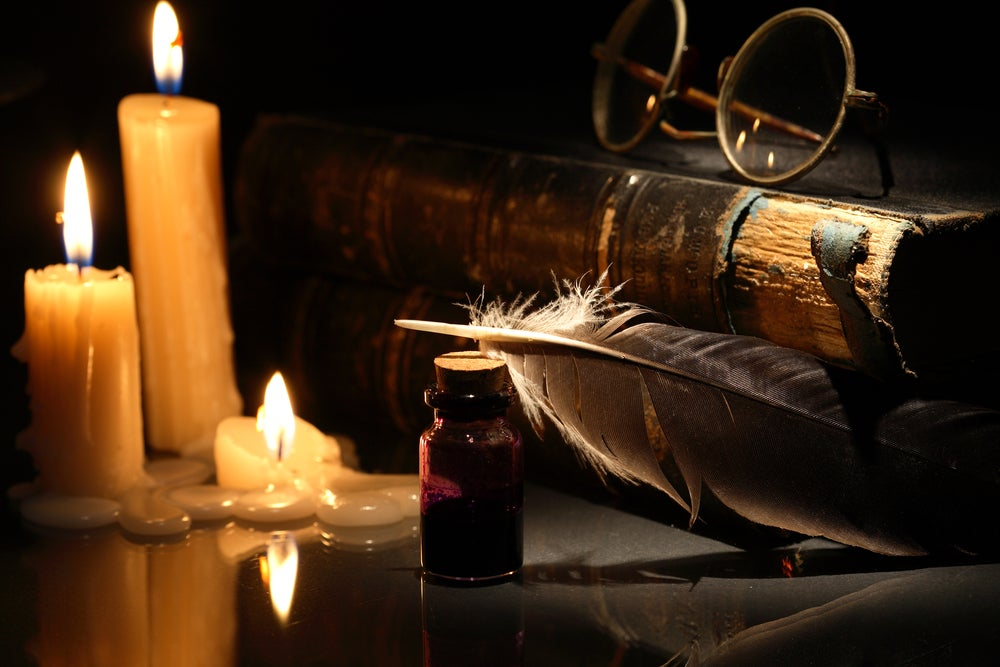 A still life of books, a quill, old spectacles, and candles