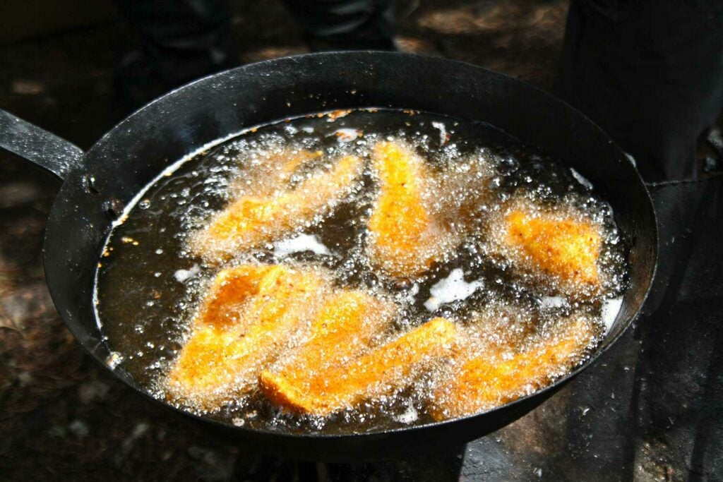 A cast iron skillet frying fillets of fish.