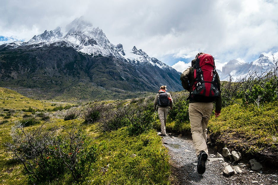 two people hiking up to a mountain
