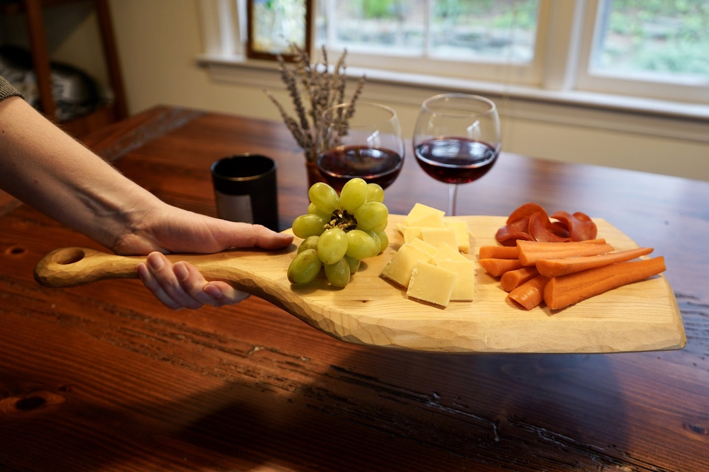 a person holding a handmade DIY cutting board with cheese, grapes, carrots, and strawberries on it