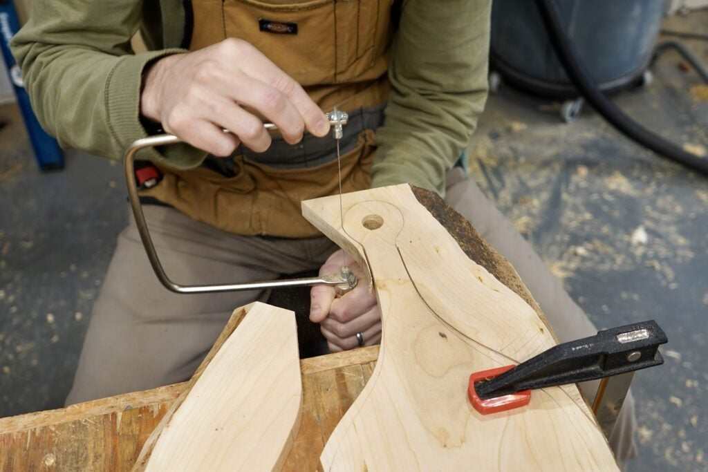 a person using a coping saw to cut the tight curves of a cutting board handle