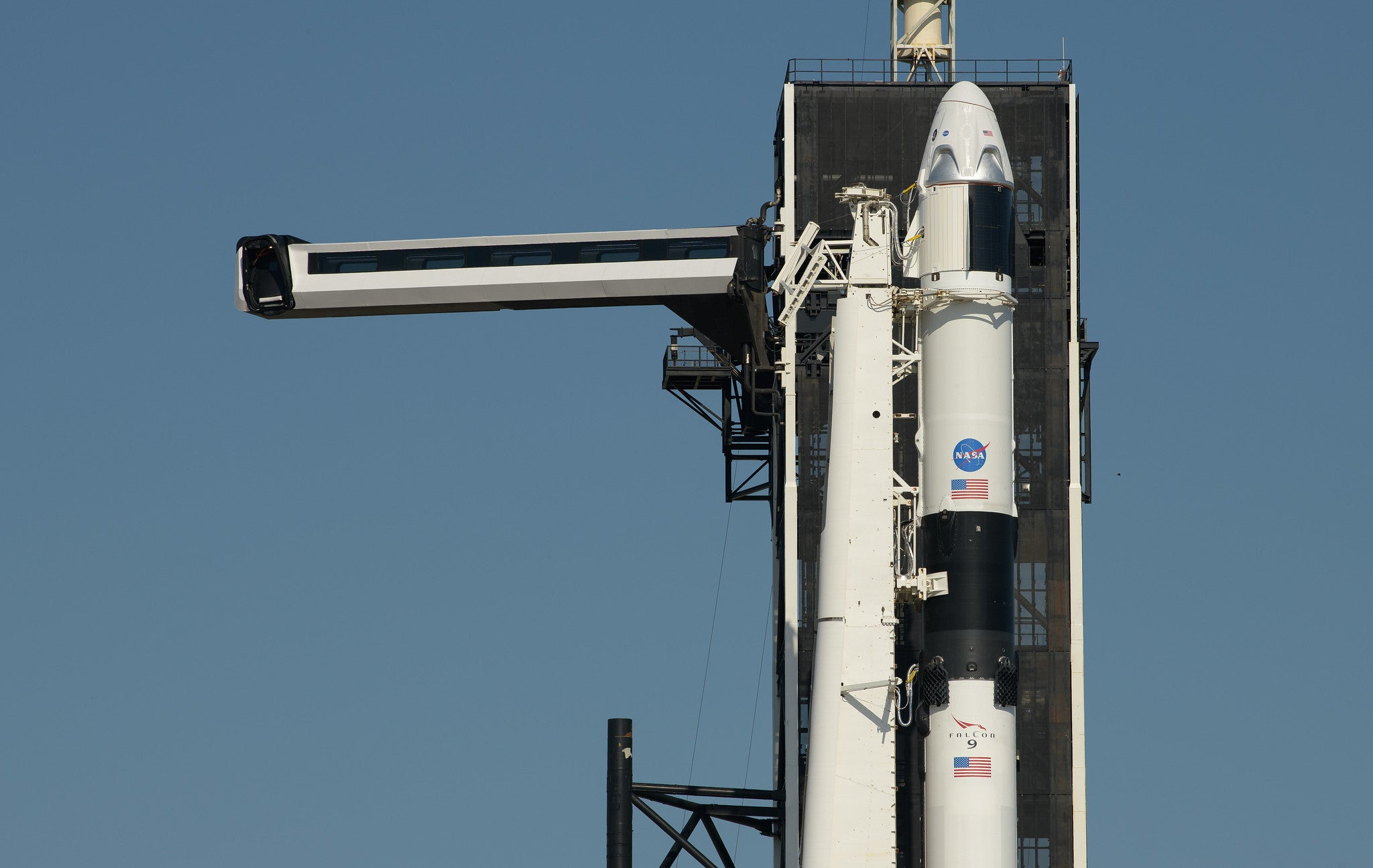 SpaceX's Crew Dragon capsule sits atop its Falcon rocket, ready to launch.