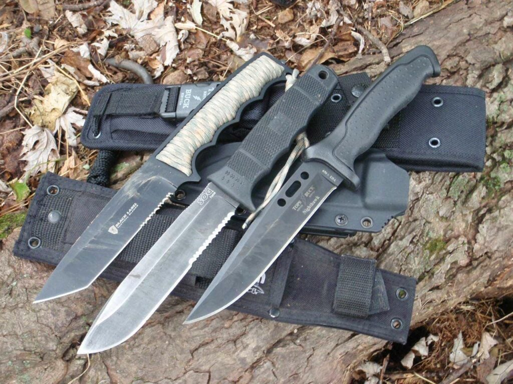 A trio of knives on a rock.