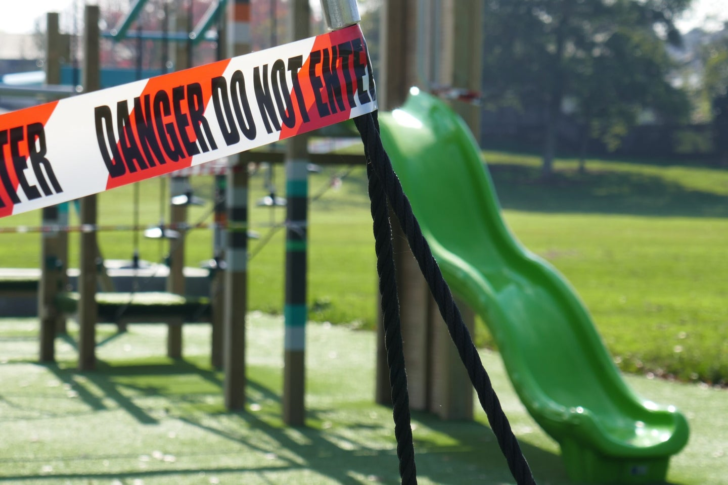 """a playground with tape around it that reads """"danger, do not enter"""""""