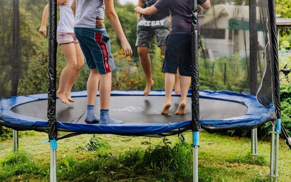 Some young teenagers having fun over a blue and big trampoline.