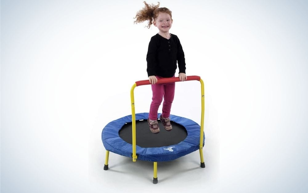 A small black and blue trampoline with a yellow holder and a girl with smiling curly hair playing on it.