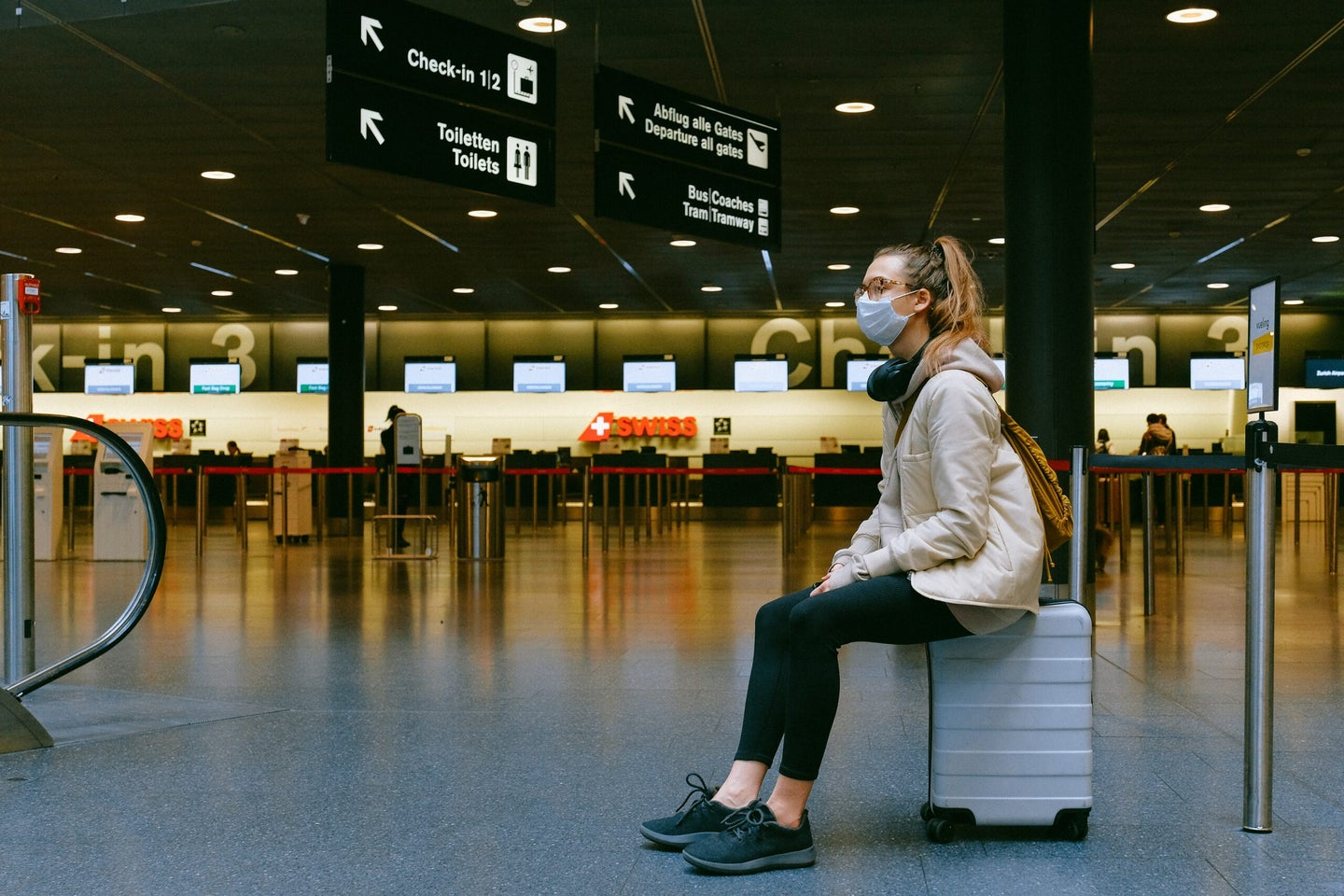 woman wearing mask sitting on suitcase in airport