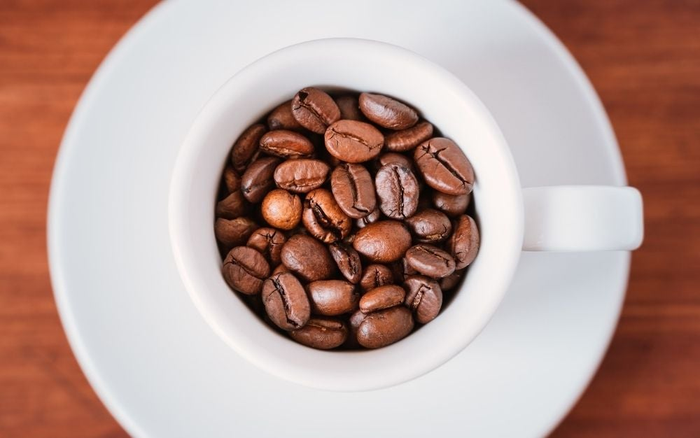 A white small coffee cup with coffee beans in brown color.