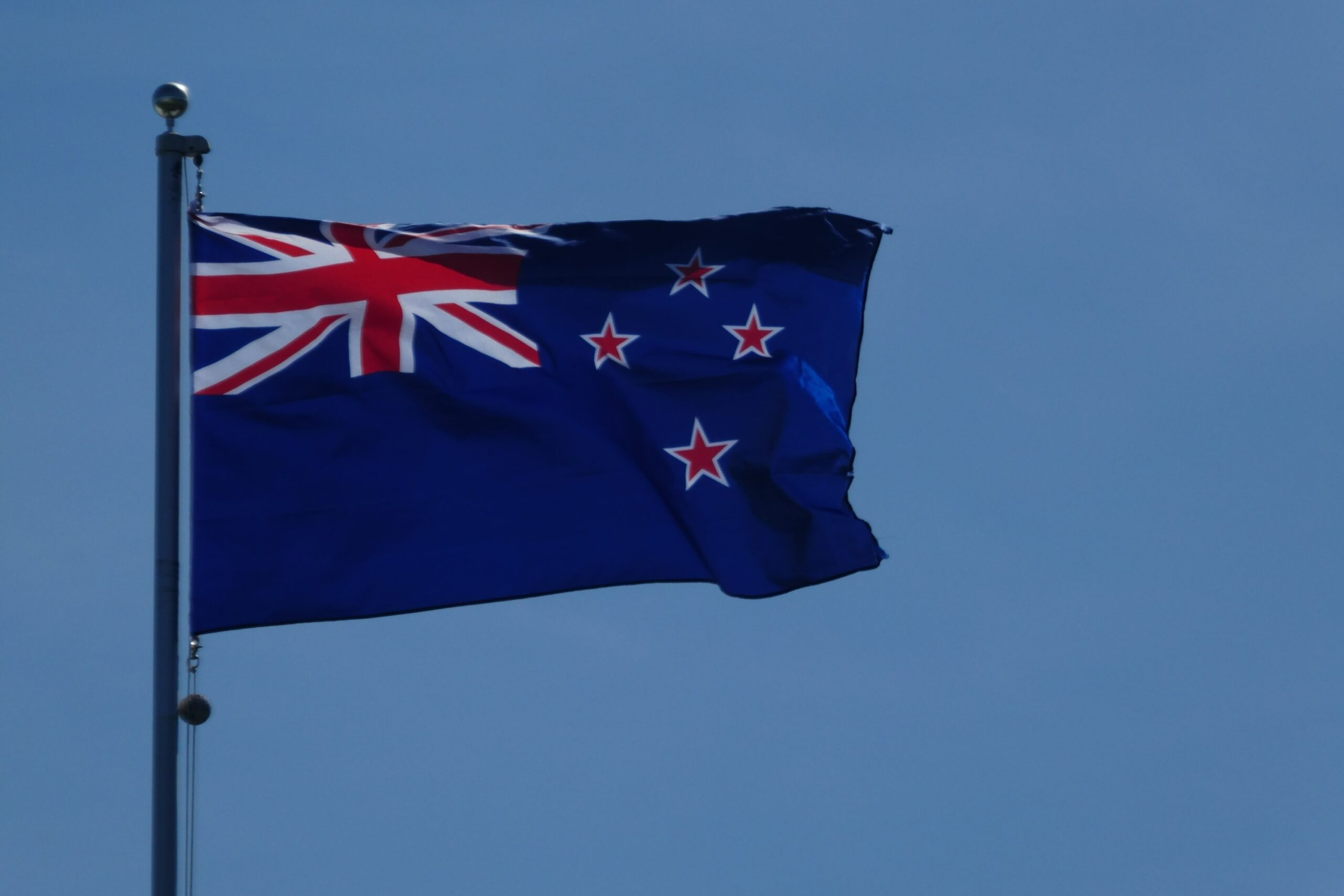 the new zealand flag on a flagpole against a blue sky