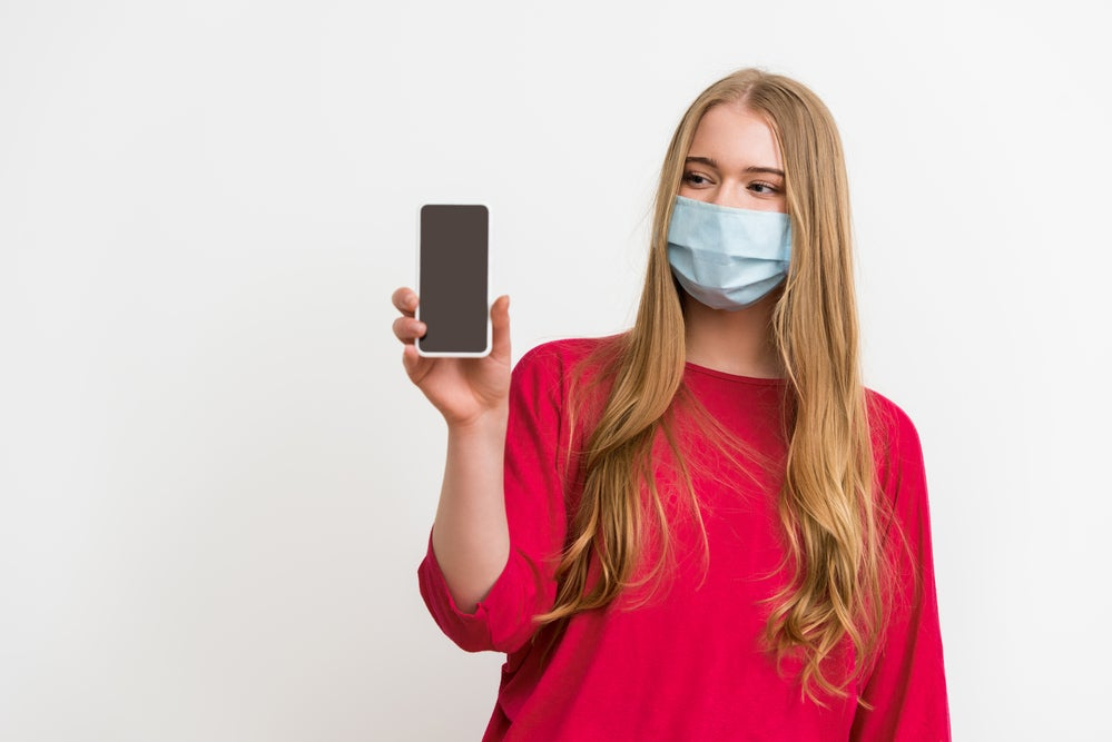 Someone holding a cellphone and wearing a mask