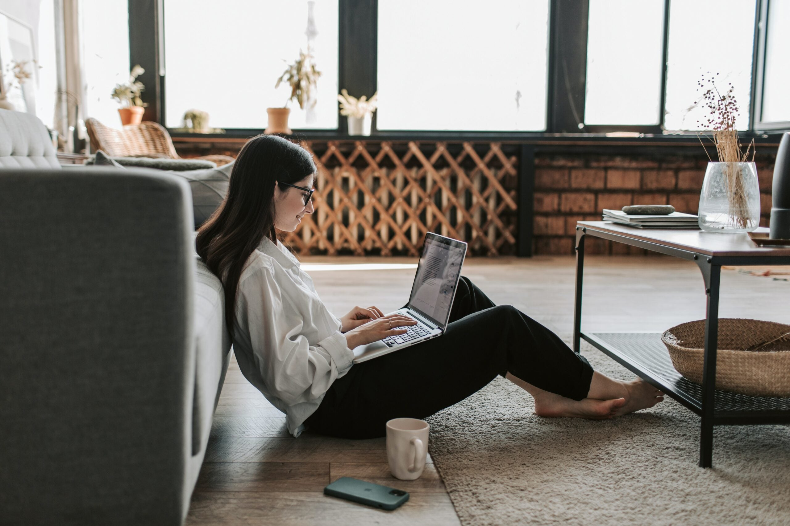 A woman working from home on the floor.
