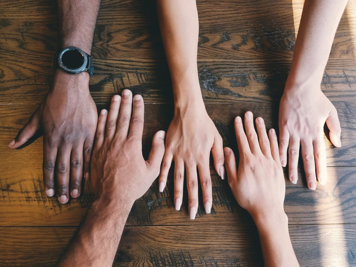four hands with different skin colors next to each other on a table