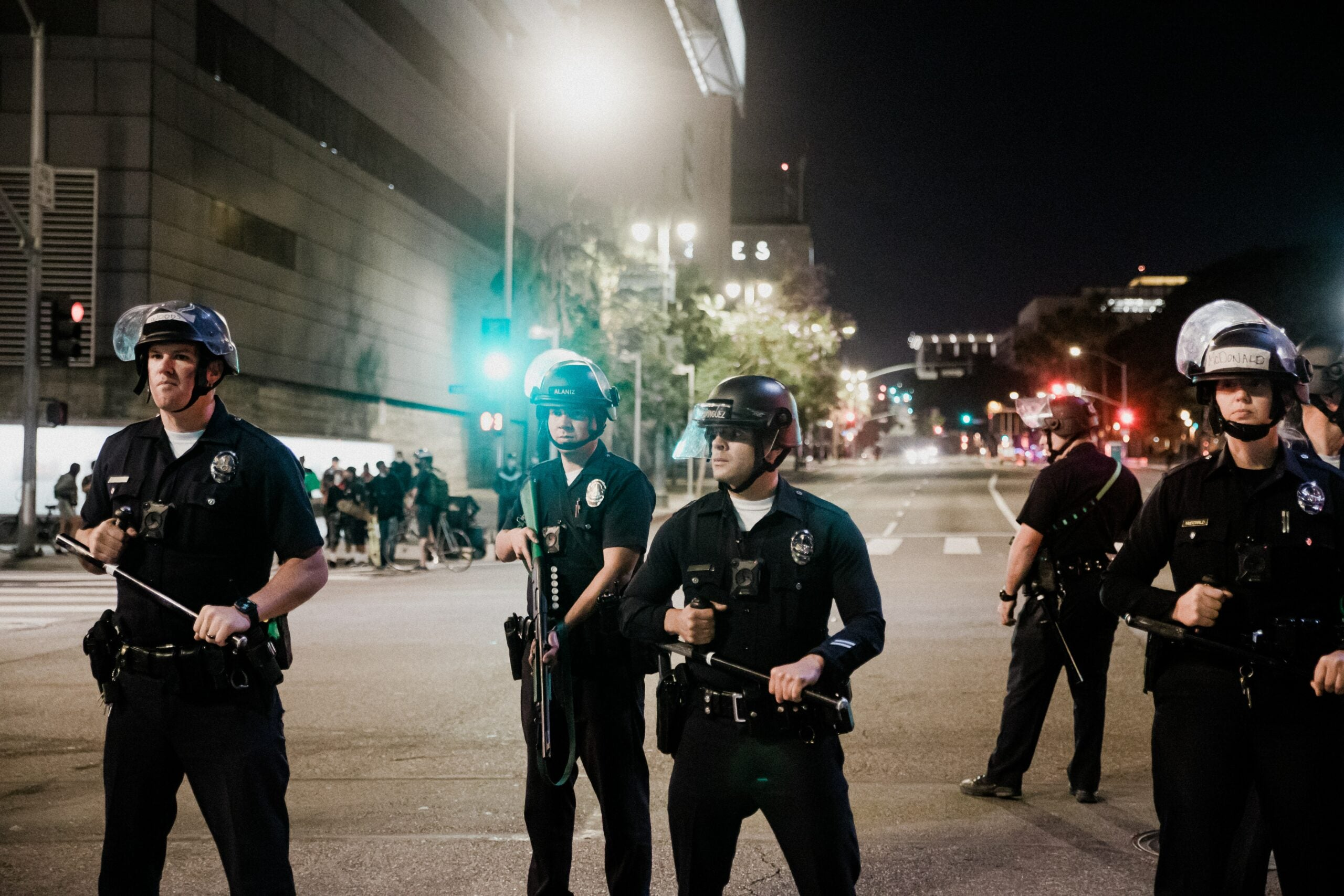 several police officers standing in a road holding weapons