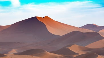 sand dunes in a desert with blue skies