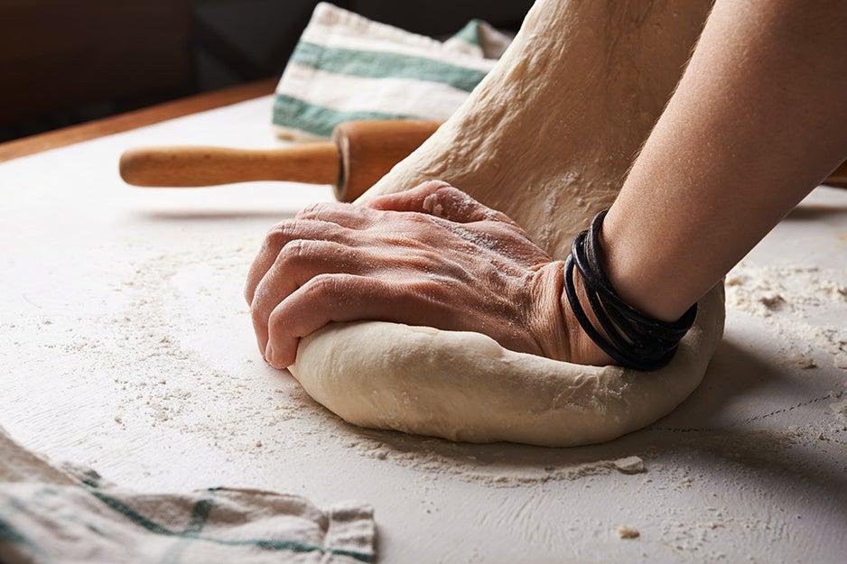 person kneading dough