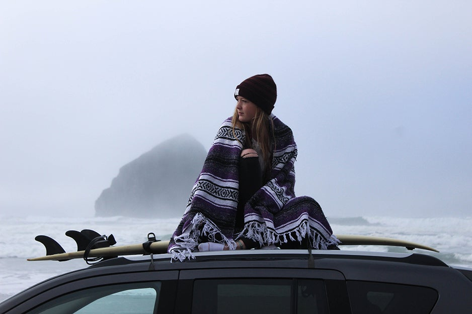 person sitting on top of a car with a blanket
