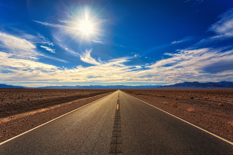 road running through hot flatlands with sun shining